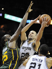 San Antonio Spurs' Manu Ginobili, center, of Argentina, shoots over Utah Jazz's Al Jefferson during the second half of an NBA basketball game, Sunday, April 8, 2012, in San Antonio. San Antonio won 114-104. (AP Photo/Darren Abate)