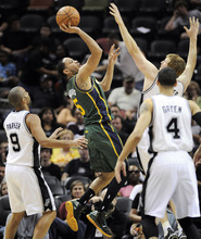 Utah Jazz's Devin Harris, center, shoots between San Antonio Spurs' Tony Parker (9), of France, Danny Green (4) and Matt Bonner during the second half of an NBA basketball game, Sunday, April 8, 2012, in San Antonio. (AP Photo/Darren Abate)