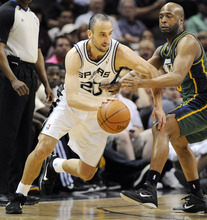 San Antonio Spurs' Manu Ginobili, left, of Argentina, drives around Utah Jazz's Jamaal Tinsley during the first half of an NBA basketball game, Sunday, April 8, 2012, in San Antonio. (AP Photo/Darren Abate)