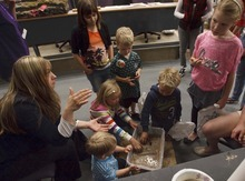 Leah Hogsten  |  The Salt Lake Tribune Weber State University senior student Sara Yearsley talks on Saturday about what happens during an earthquake as children poke their fingers into sand slurry to show how the earth liquifies during earthquake preparedness event.
