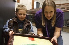 Leah Hogsten  |  The Salt Lake Tribune Calvin Clark, 6, of Ogden, and Weber State University junior Cassie Grether learn about waves and what happens during an earthquake on Saturday at Weber State University's Lind Lecture Hall during earthquake preparedness event.