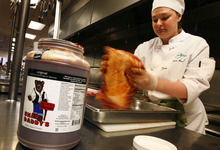 Scott Sommerdorf  |  The Salt Lake Tribune              Murray High culinary student Katie Crawford rubs Utah pork with Snap Daddy's BBQ sauce as she prepares pulled pork sandwiches that will be served during the Governor's 6th Annual Economic Summit. Utah foods will be showcased at the conference Tuesday to highlight the diversity and range of manufacturers and farmers in the state.
