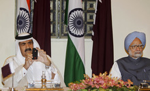Emir of Qatar, Sheikh Hamad bin Khalifa Al Thani uses his phone to take video of the signing of agreements between India and Qatar as he sits next to Indian Prime Minister Manmohan Singh at Hyderabad House in New Delhi, India, Monday, April 9, 2012.The Emir is on an official visit to India.(AP Photo/Mustafa Quraishi)