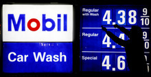A gas station attendant raises gas prices on a display at Mobil gas station in Chicago, Friday, April 6, 2012. (AP Photo/Nam Y. Huh)