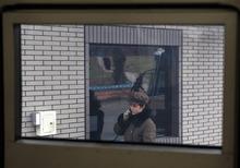 A female North Korean guard calls on the phone at the entrance to the Hana Music Information Center in Pyongyang, North Korea, Thursday, April 12, 2012. (AP Photo/Ng Han Guan)