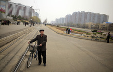 A North Korean man with a bicycle stands near residential development projects in Pyongyang, North Korea, Thursday, April 12, 2012. (AP Photo/Ng Han Guan)