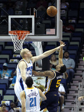 Utah Jazz point guard Devin Harris (5) shoots over New Orleans Hornets center Chris Kaman (35) in the first half of an NBA basketball game in New Orleans, Friday, April 13, 2012. (AP Photo/Gerald Herbert)