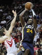 Utah Jazz's Paul Millsap (24) shoots over Houston Rockets' Chandler Parsons in the second half of an NBA basketball game Wednesday, April 11, 2012, in Houston. Utah won 103-91. (AP Photo/Pat Sullivan)