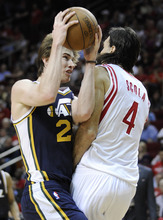 Utah Jazz's Gordon Hayward (20) is fouled by Houston Rockets' Luis Scola (4) during the second half of an NBA basketball game Wednesday, April 11, 2012, in Houston. Utah won 103-91. (AP Photo/Pat Sullivan)