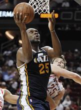 Utah Jazz's Al Jefferson, left, shoots over Houston Rockets' Chandler Parsons in the second half of an NBA basketball game Wednesday, April 11, 2012, in Houston. Utah won 103-91. (AP Photo/Pat Sullivan)