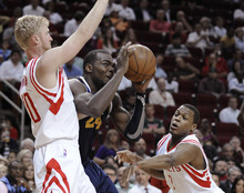 Utah Jazz's Paul Millsap (24) looks to the basket while guarded by Houston Rockets' Chase Budinger (10) and Kyle Lowry (7) in the first half of an NBA basketball game Wednesday, April 11, 2012, in Houston. (AP Photo/Pat Sullivan)