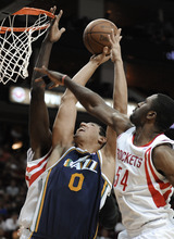 Utah Jazz's Enes Kanter (0) goes to the basket between Houston Rockets' Patrick Patterson (54) and Samuel Dalembert in the first half of an NBA basketball game Wednesday, April 11, 2012, in Houston. (AP Photo/Pat Sullivan)