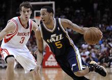 Utah Jazz's Devin Harris (5) drives the ball around Houston Rockets' Goran Dragic (3) in the first half of an NBA basketball game Wednesday, April 11, 2012, in Houston. (AP Photo/Pat Sullivan)