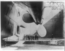 Library of Congress photo  Workers stand below one of the Titanic's giant propellers before the ship was launched.