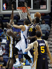 New Orleans Hornets shooting guard Eric Gordon goes to the basket between Utah Jazz power forward Paul Millsap (24) and center Al Jefferson (25) in the second half of an NBA basketball game in New Orleans, Friday, April 13, 2012. The Hornets won 96-85. (AP Photo/Gerald Herbert)