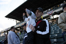 Kim Raff | The Salt Lake Tribune Mark Bevans holds his son Jackson Bevans at the Bees homeopener against Tucson Padres at Spring Mobile Ballpark in Salt Lake City, Utah on April 13, 2012.