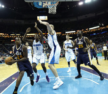 Utah Jazz power forward Paul Millsap (24) tries to shoot around New Orleans Hornets small forward Al-Farouq Aminu (0) and center Chris Kaman in the second half of an NBA basketball game in New Orleans, Friday, April 13, 2012. The Hornets won 96-85. (AP Photo/Gerald Herbert)