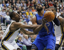 Utah Jazz guard Alec Burks, left, fouls Dallas Mavericks guard Vince Carter (25) during the first half of an NBA basketball game, Monday, April 16, 2012, in Salt Lake City.  (AP Photo/Colin E Braley)