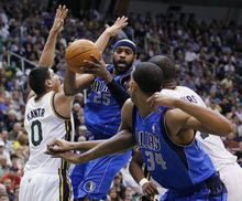 Dallas Mavericks guard Vince Carter (25) attempts to pass the ball off to forward Brandan Wright (34) as Utah Jazz forward Enes Kanter (0) defends during the first half of an NBA basketball game, Monday, April 16, 2012, in Salt Lake City. (AP Photo/Colin E Braley)