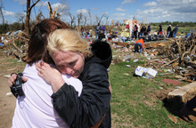 Sara Shogren, left, is hugged by Zoey Patrick as friends sort through the rubble of the Patrick's home, Sunday, April 15, 2012, in Marquette, Kans. Residents of several states scoured through the wreckage of battered homes and businesses after dozens of tornadoes blitzed the Midwest and Plains Saturday night. (AP Photo/Salina Journal, Tom Dorsey)