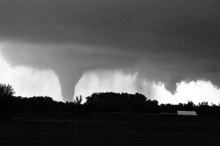 Sandra J. Milburn  |  The Hutchinson News A tornado moves on the ground north of Solomon, Kan., on Saturday evening, with I-70 seen in the foreground.
