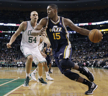 Utah Jazz forward Derrick Favors (15) drives against Boston Celtics center Greg Stiemsma (54) in the first half of an NBA basketball game in Boston, Wednesday, March 28, 2012. (AP Photo/Elise Amendola)