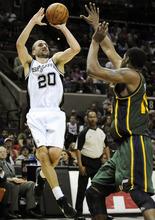 San Antonio Spurs' Manu Ginobili (20), of Argentina, shoots over Utah Jazz's Derrick Favors during the second half of an NBA basketball game, Sunday, April 8, 2012, in San Antonio. San Antonio won 114-104. (AP Photo/Darren Abate)