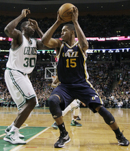 Utah Jazz forward Derrick Favors (15) looks for room against Boston Celtics power forward Brandon Bass (30) in the first half of an NBA basketball game in Boston, Wednesday, March 28, 2012. (AP Photo/Elise Amendola)