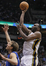 Utah Jazz center Al Jefferson, right, goes up to score against Dallas Mavericks power forward Dirk Nowitzki (41) of Germany during triple overtime in an NBA basketball game, Monday, April 16, 2012, in Salt Lake City.  Jefferson scored 28-points in the Jazz 123-121 win. (AP Photo/Colin E Braley)