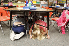 Trent Nelson  |  The Salt Lake Tribune First graders at Granite Elementary duck and cover under their desks during a statewide earthquake drill Tuesday, April 17, 2012 in Sandy, Utah.