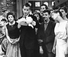 FILE - In this 1957 file photo, Dick Clark is seen surrounded by fans during a television broadcast of