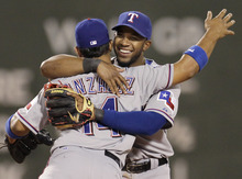 Texas Rangers shortstop Elvis Andrus celebrates with second baseman Alberto Gonzalez (14) after the Rangers defeated the Boston Red Sox 18-3 in a baseball game at Fenway Park in Boston, Tuesday, April 17, 2012. (AP Photo/Elise Amendola)