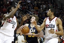 Utah Jazz's Gordon Hayward, center, drives to the basket as Portland Trail Blazers' Hasheem Thabeet (34) and Nicolas Batum, right, defend during the first quarter of an NBA basketball game Wednesday, April 18, 2012, in Portland, Ore.  (AP Photo/Rick Bowmer)