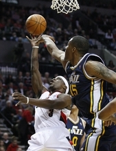 Utah Jazz's Derrick Favors (15) defends Portland Trail Blazers' Jonny Flynn (3) during the second quarter during of NBA basketball game Wednesday, April 18, 2012, in Portland, Ore.  (AP Photo/Rick Bowmer)