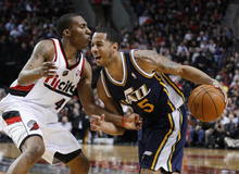 Utah Jazz's Devin Harris (5) drives to the basket as Portland Trail Blazers' Nolan Smith (4) defends during the first quarter of an NBA basketball game Wednesday, April 18, 2012, in Portland, Ore. (AP Photo/Rick Bowmer)