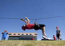 Jen Narewski makes her way across a zip line as her son, Aidan Congleton, right, looks on during the Dixie State College ROTC
