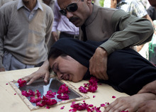 A man comforts a woman who cries over a coffin of her family member who was killed in Friday's passenger plane crash, at a local hospital in Islamabad, Pakistan on Saturday, April 21, 2012. Pakistan blocked the head of an airline whose jet crashed near the capital from leaving the country as it began an investigation Saturday into the country's second major air disaster in less then two years. (AP Photo/B.K. Bangash)
