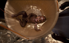 Halime Ali, 13 months old, lies in the plastic bucket of a weighing scale to have her weight checked for signs of malnutrition at a walk-in feeding center in Dibinindji, a desert village in the Sahel belt of Chad, Wednesday, April 18, 2012. UNICEF estimates that 127,000 children under 5 in Chad's Sahel belt will require lifesaving treatment for severe acute malnutrition this year, with an estimated 1 million expected throughout the wider Sahel region of West and Central Africa in the countries of Niger, Nigeria, Mali, Chad, Burkina Faso, Cameroon, Senegal and Mauritania. The organization says the current food and nutrition crisis stems from scarce rainfalls in 2011, which caused poor harvests and livestock production, though the situation in Chad has also been exacerbated by an influx of Chadians returning from Libya as a result of the conflict there. (AP Photo/Ben Curtis)