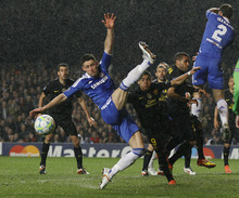 Chelsea's Gary Cahill, left, watches the ball go past after an attempted clearance as Barcelona's Andres Iniesta, center, looks on during their Champions League semifinal first leg soccer match at Chelsea's Stamford Bridge stadium in London,Wednesday, April 18, 2012. (AP Photo/Kirsty Wigglesworth)