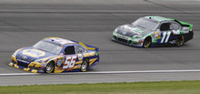 Martin Truex Jr. (56) leads Denny Hamlin (11) into Turn 2 during the NASCAR Sprint Cup Series auto race at Kansas Speedway in Kansas City, Kan., Sunday, April 22, 2012. (AP Photo/Orlin Wagner)