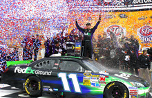 Denny Hamlin (11) stands on his car in victory lane after winning the NASCAR Sprint Cup Series auto race at Kansas Speedway in Kansas City, Kan., Sunday, April 22, 2012. (AP Photo/Autostock, Russell LaBounty) MANDATORY CREDIT