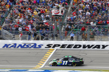 Denny Hamlin (11) drives under the checkered flag to win the NASCAR Sprint Cup Series auto race at Kansas Speedway in Kansas City, Kan., Sunday, April 22, 2012. (AP Photo/Autostock, Russell LaBounty) MANDATORY CREDIT