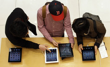 Visitors to an Apple store look at new iPad tablet computers in Seoul, South Korea, Friday, April 20, 2012. (AP Photo/Lee Jin-man)