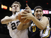 Utah Jazz's Enes Kanter, right, fights for the ball with San Antonio Spurs' Tiago Splitter, of Brazil, during the second half of an NBA basketball game, Saturday, Dec. 31, 2011, in San Antonio. San Antonio won 104-89. (AP Photo/Darren Abate)