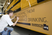 Paul Fraughton | The Salt Lake Tribune. Daniel Johnson, of Wrap Star, puts  the finishing touches on an ad placed on a Jordan District school bus. The district had the ad  put on four of their buses  with plans to do more.  Money generated from the ads  will stay in the transportation dept.The district will review all advertising, making sure it complies  with guidelines  they established.  Tuesday, April 24, 2012