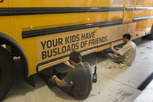 Paul Fraughton | The Salt Lake Tribune. Daniel Johnson,right,  and Jaren O' Farrell, of Wrap Star  put the finishing touches on an ad they placed on a Jordan District school bus. The district had the ad  put on four of their buses  with plans to do more.  Money generated from the ads  will stay in the transportation dept.The district will review all advertising, making sure it complies  with guidelines  they established.  Tuesday, April 24, 2012