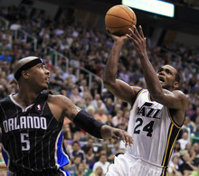 George Frey  |  The Associated Press Utah Jazz's Paul Millsap, right, shoots past Orlando Magic's Quentin Richardson during the second half of an NBA basketball game in Salt Lake City, Saturday, April 21, 2012. The Jazz beat the Magic 117-107 in overtime.