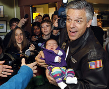 Republican presidential candidate, former Utah Gov. Jon Huntsman holds eight-week-old Grace Lesperance while campaigning at Mary's Bakery and Cafe in Henniker, N.H., on Monday, Jan. 9, 2012. (AP Photo/Elise Amendola)