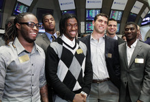 From left, NFL football draft prospects Trent Richardson, of Alabama, Robert Griffin III, of Baylor, Andrew Luck, of Stanford, and Justin Blackmon, of Oklahoma State, pose for photos during their visit to the trading floor of the New York Stock Exchange, Wednesday, April 25, 2012. The college stars are preparing for the NFL draft Thursday night at Radio City Music Hall. (AP Photo/Richard Drew)