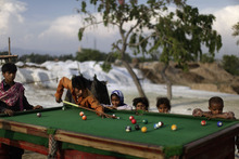 Pakistani men who were displaced by 2010 floods from a village near Multan, plays a game of pool in a slum on the outskirts of Islamabad, Pakistan, Tuesday, April 24, 2012. (AP Photo/Muhammed Muheisen)